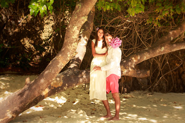 bride sitting on tree and hold her groom