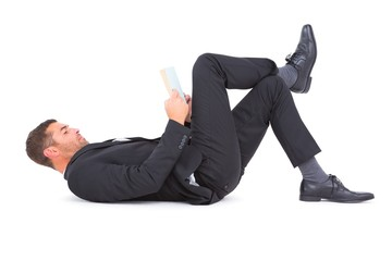 Businessman lying on the floor reading book