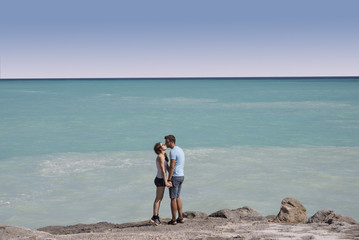 Happy couple kissing on a beach on holidays