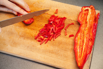 Slicing red sweet pepper on wooden board