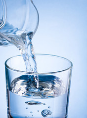 Close-up pouring water from a jug into glass on a blue backgroun