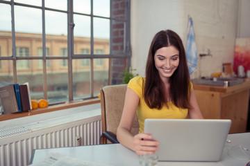 frau schaut lächelnd auf ihren laptop