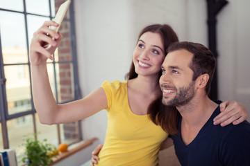 glückliches paar macht ein selfie zu hause