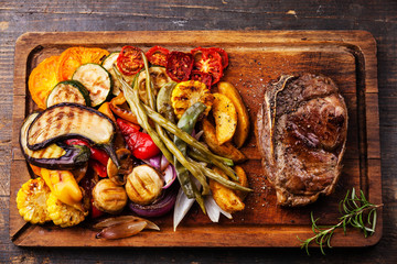Club Beef steak and Grilled vegetables on cutting board on dark