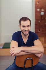 lächelnder mann sitzt auf einem stuhl