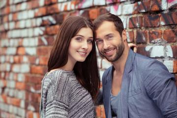 glückliches junges paar lehnt an einer backstein-wand