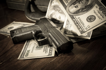 Sepia filtered of gun and dollar bills
