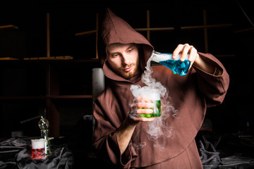 Alchemist in chemical laboratory prepares magical liquids