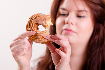 Woman eating a donut using her fingers