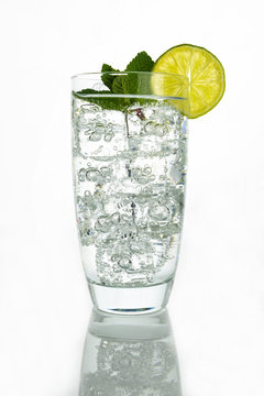 Glass o sparkling water with ice cubes on white background