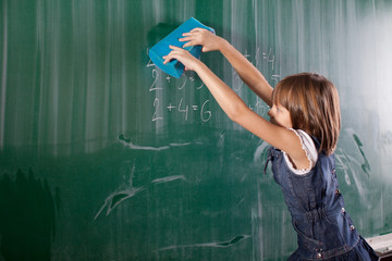 Little girl in elementary school cleaning board with spong