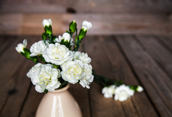 delicate bouquet of carnations in vintage vase with heart