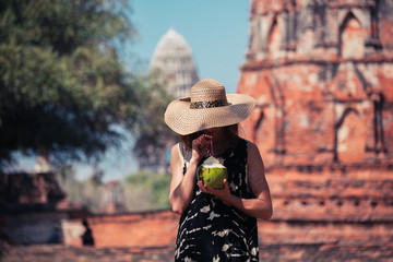 Woman drinking coconut juice by ancient temple