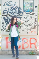 Young beautiful asian woman posing against wall with graffiti