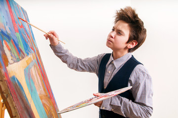 artist school boy painting brush watercolors portrait on a easel