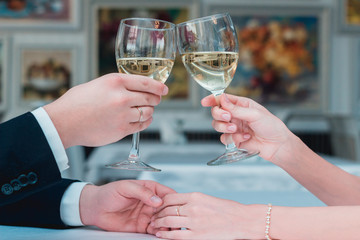 Newlyweds holding glasses of wine holding hands.