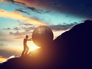 Sisyphus metaphor. Man rolling huge concrete ball up hill.