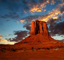 Monument Valley, USA colorful sunrise or sunset with dramatic clouds, desert landscape of Navajo Nation Park in Utah and Arizona, a famous travel destination for it's red rock formations
