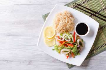 Rice noodles and vegetable salad with squid horizontal top view