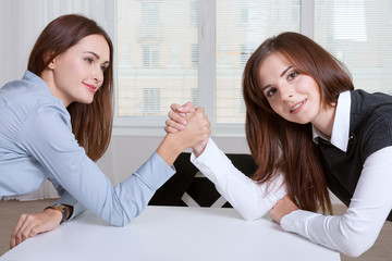 Women finance competitive worker while armwrestling