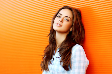 Portrait pretty sensual woman outdoors against colorful wall