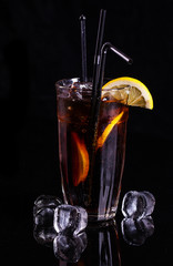 Glass of cola with ice and lemon.