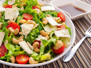 Green salad with brie, cashew and cherry tomatos