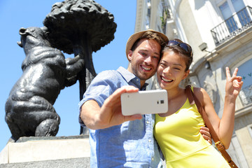 Tourists taking selfie photo by bear statue Madrid