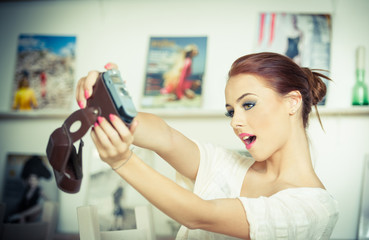 Beautiful, smiling red hair woman taking photos of herself