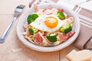 Tagliatelle pasta with broccoli, prosciutto and fried egg.