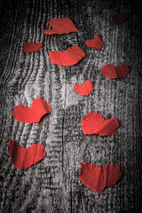 Many Valentine hearts on the old wooden table. Toned.