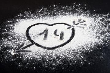Shape of heart with arrow drawn on the flour on a black backgrou