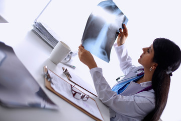 Young female doctor studying x-ray image, sitting at the desk