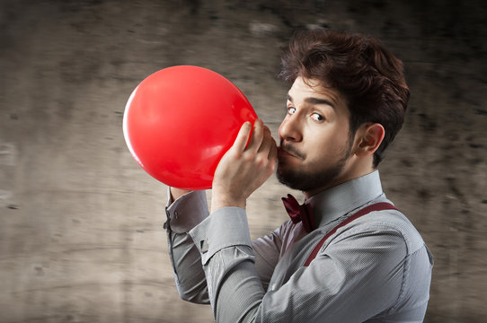Man inflating a red balloon by mouth