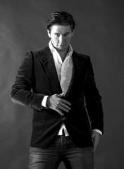 Elegant smiling young handsome man on a dark background