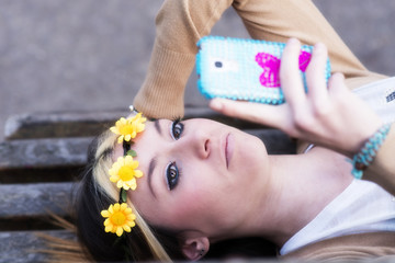 Happines beautiful girl with smart phone lying on the bench.