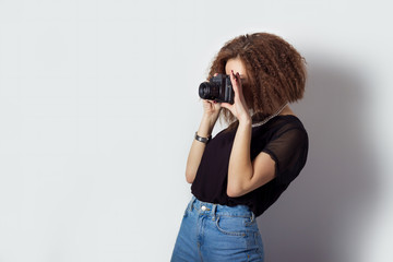 young girl hipster makes the images photographs on the camera