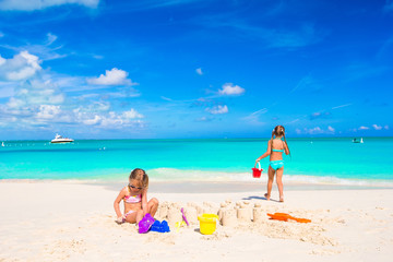 Little sisters playing with beach toys during tropical vacation
