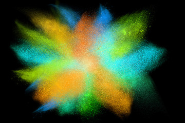 Freeze motion of colorful powder exploding on black background
