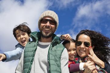 Familia feliz sonriendo con cielo azul de fondo