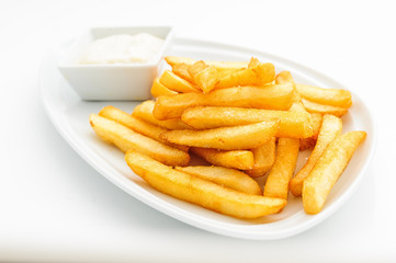 Fried potatoes on white plate with sauce