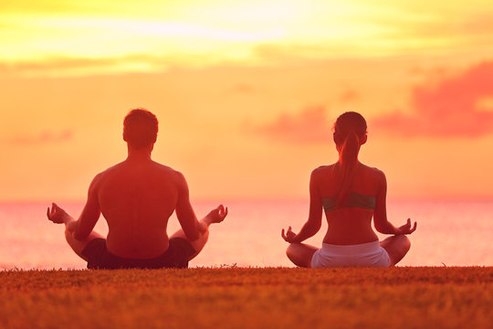 Meditation yoga couple meditating at beach sunset