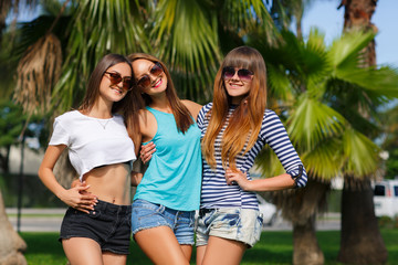 Three girls on the background of palm trees