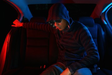 Man in the backseat of a car wearing a hoodie shirt