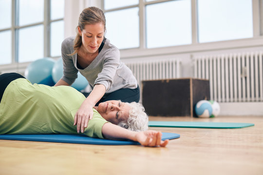 Female trainer helping elder woman in stretching