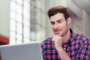 mann schaut auf seinen laptop