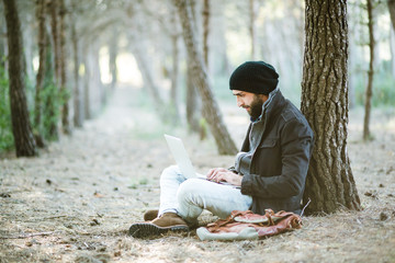urban man using laptop while sitting on land in forest