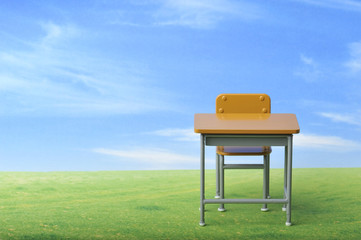 青空の下に置いてある学校の机