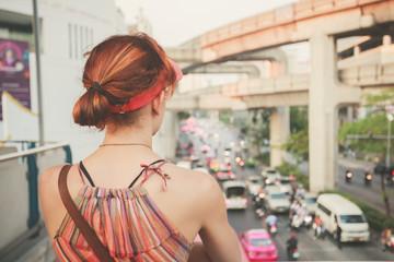 Young woman looking at traffic in Bangkok