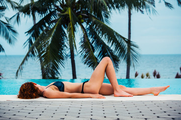 Sexy young woman lying by swimming pool